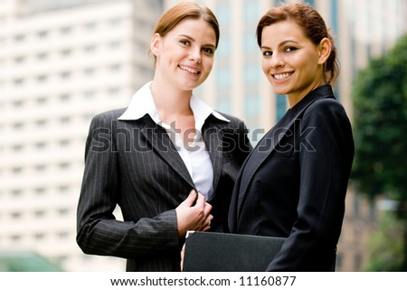 Two young businesswoman in the city with buildings behind - stock photo