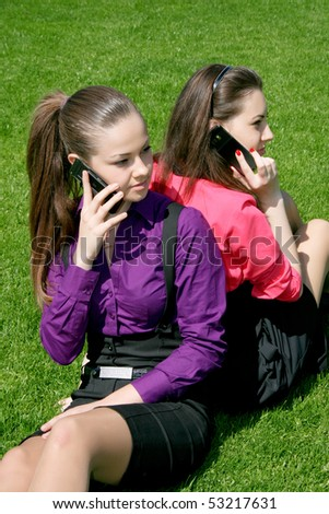 Two young businesswomen calling by phone