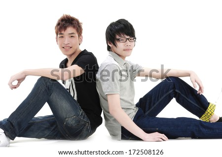 two young casual men sitting back to back on white background and looking at the camera , smiling