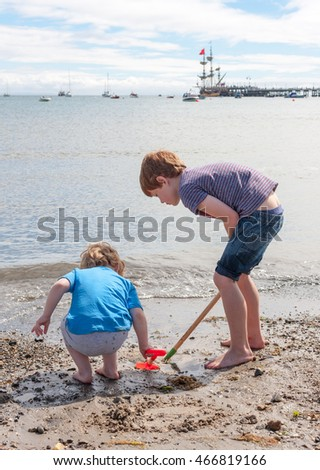 Two young caucasian boys playing on the beach with toy spades