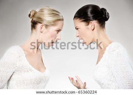 two young caucasian women arguing, studio shot - stock photo