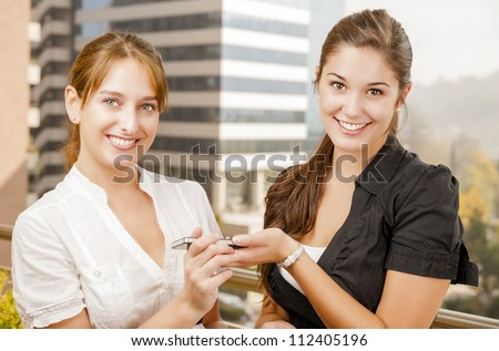 Two young caucasian women sharing a phone call in a work environment - stock photo
