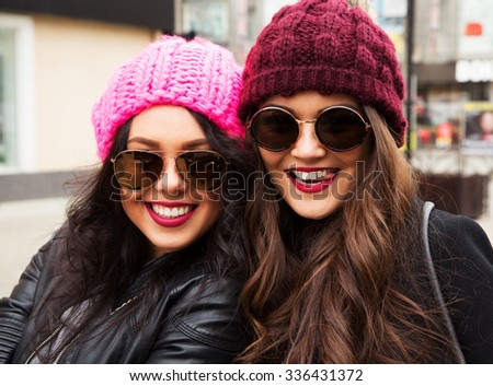 Two young cheerful best girls friends tongue sticking out!  Smiling and walking on the autumn city. Wearing stylish outerwear with sunglasses and hats. Outdoors lifestyle fashion close up portrait - stock photo