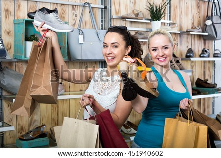 Two young cheerful woman shopping together in the fashion store - stock photo
