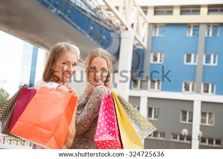 Two young cheerful women with shopping bags outdoors - stock photo