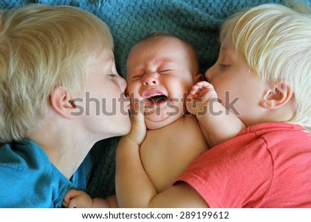 Two young children, a little boy and his toddler brother are kissing their chubby newborn baby sister as she cries. - stock photo