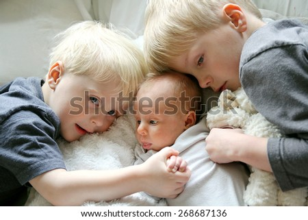 Two young children, a toddler and his big brother are lovingly hugging their newborn baby sister., and holding hands - stock photo