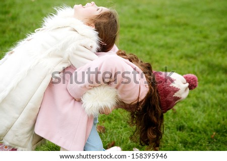 Two young children and family sisters playing together in a park with green grass during a cold winter day, wearing coats and having fun outdoors. - stock photo