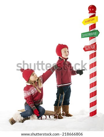 Two young children are on their way to the North Pole.  The sister points the way on one of Santa's directional signs.  On a white background with plenty of space for your text. - stock photo