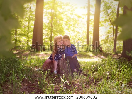 Two young children are sitting on a tree stump in the sunshine with green leaves in the woods for a relaxation or nature concept. - stock photo