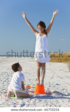 Two young children, boy and girl, brother and sister, playing on a beach making sandcastles - stock photo