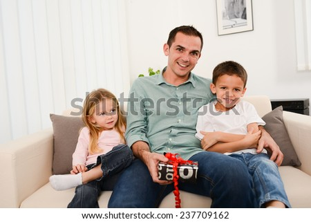Two young children boy and girl offering a present to daddy at home - stock photo