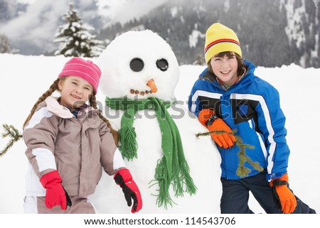 Two Young Children Building Snowman On Ski Holiday In Mountains - stock photo
