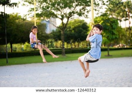 Two young children dangling on the suspension rope in playground - stock photo