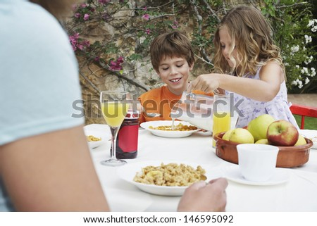 Two young children having breakfast at the outdoor table