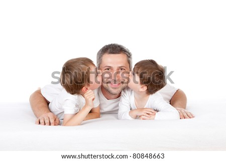 Two young children kissing their father while lying on a bed.  White background