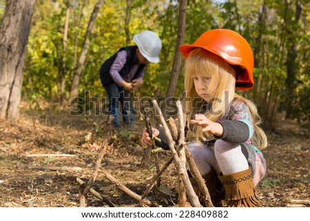 Two young children playing at being builders outdoors in the woods as they collect twigs to build a wooden framework in their hardhats with focus to a little blond girl in the foreground - stock photo