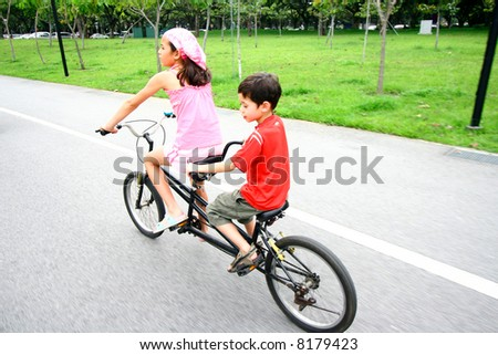 Two young children riding on a tandem bike. - stock photo