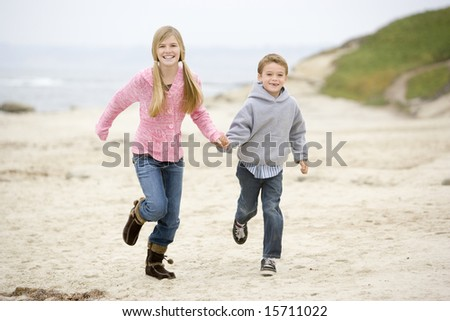 Two young children running on beach holding hands smiling - stock photo