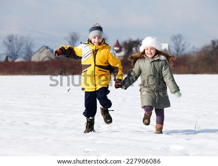 Two young children running on snow holding hands smiling - stock photo