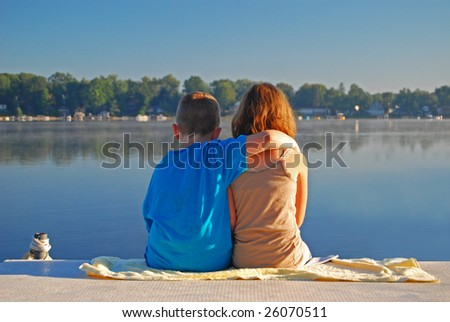 two young children show their affection in the early morning at the lake - stock photo