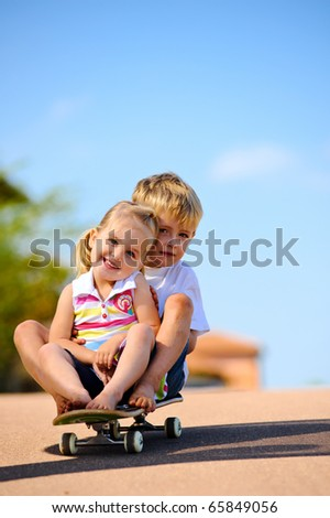 Two young children sitting and playing with skateboard - stock photo