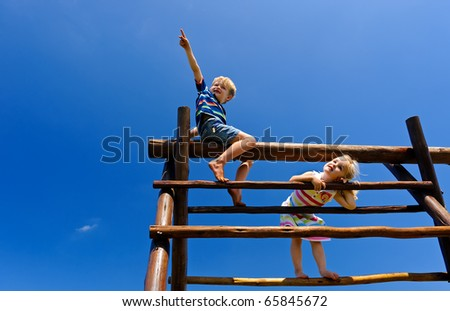 Two young children sitting at the top of playground equipment - stock photo