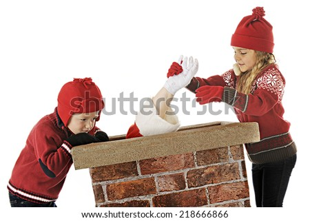 Two young children trying to help Santa back up the chimney.  On a white background. - stock photo