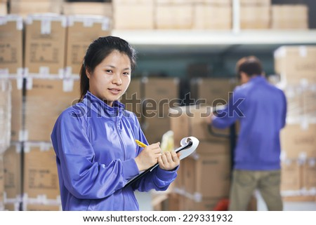 two young chinese workers in uniform in discussing warehousing system - stock photo
