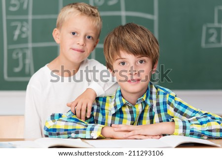 Two young classmates in school posing in front of the blackboard at their desk with one little boy leaning on the shoulder of the second - stock photo