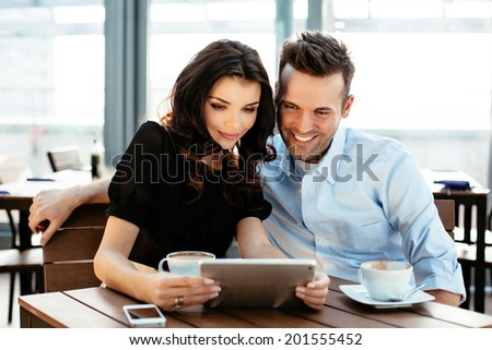 Two young colleagues enjoying a coffee and surfing on a digital tablet - stock photo