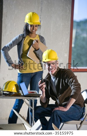 Two young construction workers - stock photo