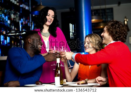 Two young couples in club or bar having fun, toasting wine glasses.