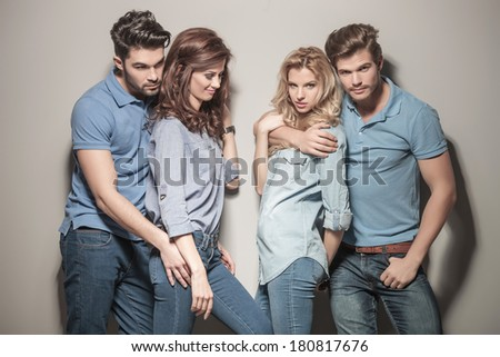two young couples of casual people standing embraced near each other - stock photo