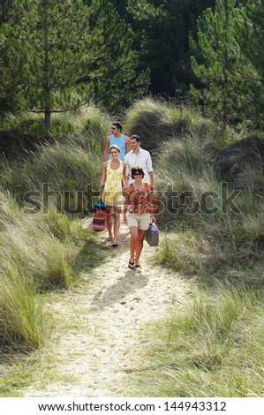 Two young couples walking on trail to beach - stock photo