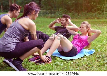Two young couples working out in a park with one couple doing sit ups assisted by the second man and woman holding their feet - stock photo