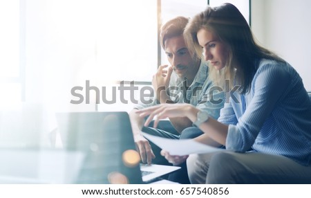 Two young coworkers working on laptop computer at sunny office.Woman holding paper documents and pointing on notebook screen. Horizontal.Blurred background