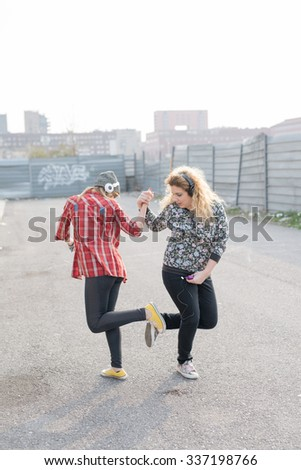 Two young curly and straight blonde hair caucasian woman listening music with headphones, dancing in the streets of the city - music, relaxing, friendship concept - stock photo
