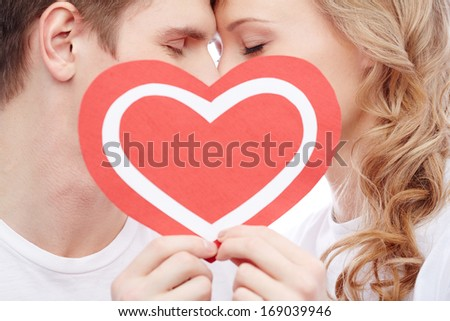 Two young dates behind paper heart with their faces close to one another - stock photo