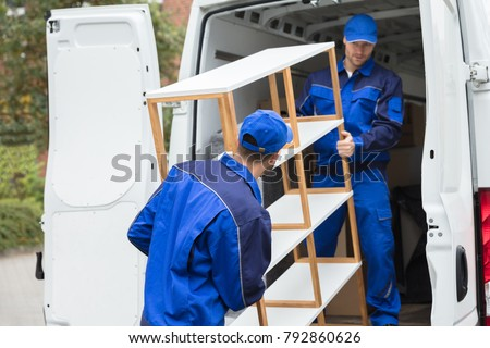 Two Young Delivery Men In Uniform Unloading Wooden Shelf From Truck