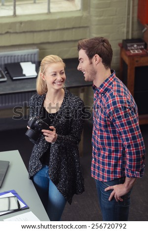 Two young designers or photographers standing in a studio holding a camera preparing to take product shots and smiling and laughing together, high angle view - stock photo