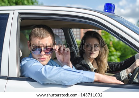 Two young detectives driving to crime scene. - stock photo