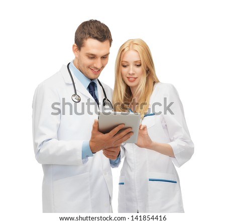 two young doctors working with tablet pc - stock photo