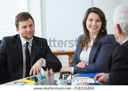Two young elegant employees talking with their elderly boss - stock photo
