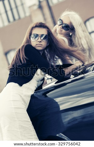 Two young fashion women in sunglasses by retro car