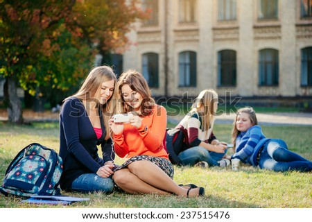 Two young female caucasian students using smart phone together and smiling while two women sitting in the background outdoors - stock photo