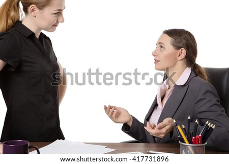 two young, female co-workers in an office.  One sitting at a desk wearing a suit and another standing opposite, having a conversation.