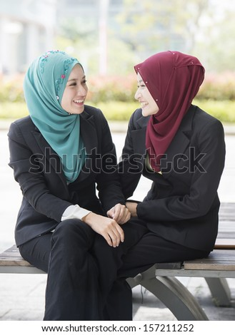 Two Young Female Executives wearing scarf having happy conversation. - stock photo