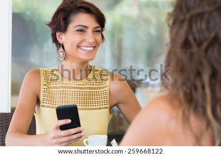 Two Young Female Friends Chatting With Each Other At Coffee Bar  - stock photo