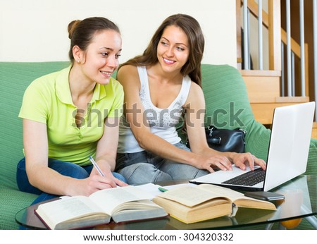 Two young female students sitting on sofa and doing homework at home